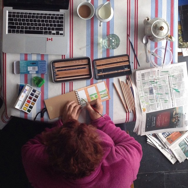 This photo contains all the things that make me happy, whether at home or far away: painting, writing, a pot of tea and a stack of newspapers